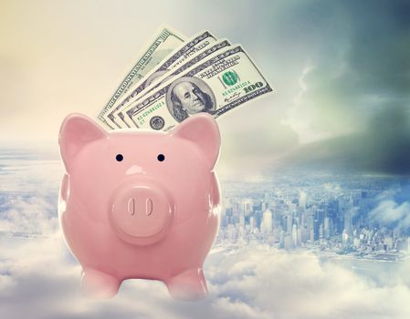 Piggy bank with hundred dollar bills above the city