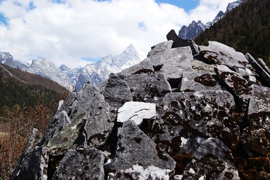 Tibetan Buddhist temple by snow mountain in Daocheng,Sichuan Province, China