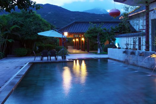 Chinese style hot spring pool with dragon head statues flowing out water