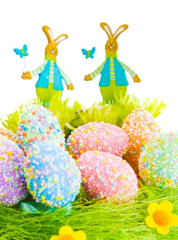 Beautiful Easter still life, colorful eggs on green grass decorated with cute bunny toy, happy holiday
