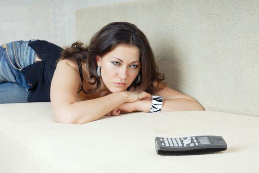 Sad woman looking at the phone and waiting call