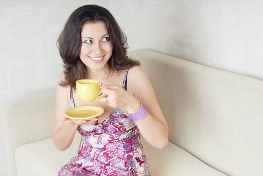 Smiling lady with teacup sitting on a sofa and looking aside