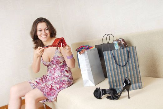 Laughing lady with empty purse sitting on a sofa with purchase