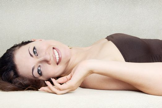 Photo of the smiling woman pampering on a sofa