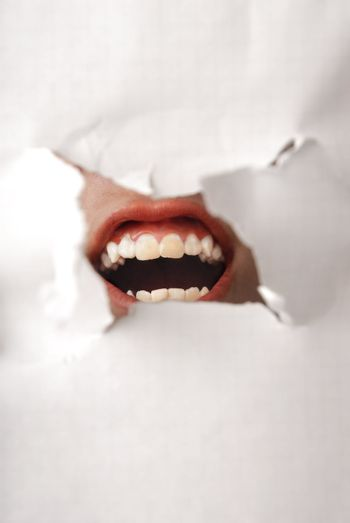 Screaming human mouth behind the damaged paper