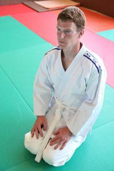 Kneeling man on judo mat