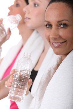 Sportswomen hydrating after effort