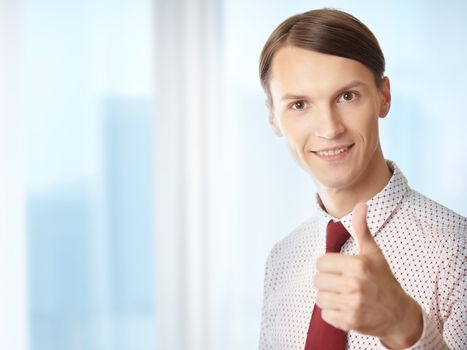 Successful businessman making thumbs up gesture in his office