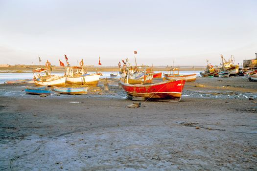 Dwarka Roadtrip. Landscape of an orange evening sun falling on banked and grounded fishing boats and ferries in Gujarat India. Hazy blue sky and silty foreground with motorbike tire marks