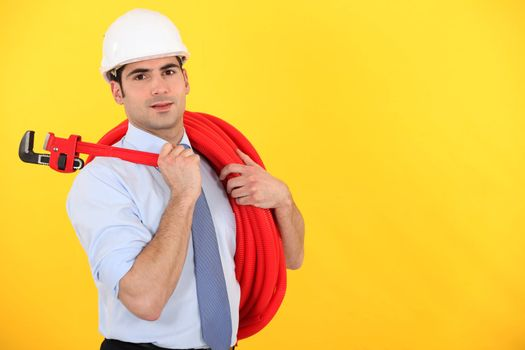 Man holding wrench and coiled pipe