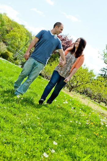 Young happy couple enjoying each others company outdoors through a country field.