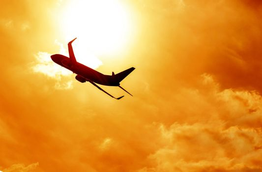 Airplane silhouette on sunset background