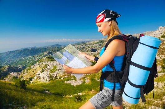 Woman on the mountain watching in map