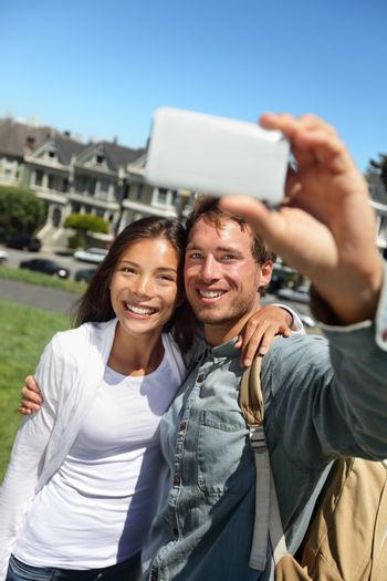 Couple fun taking self-portrait photo with cell phone camera. Multiracial happy tourist couple on travel vacation in San Francisco, Alamo Square, USA.