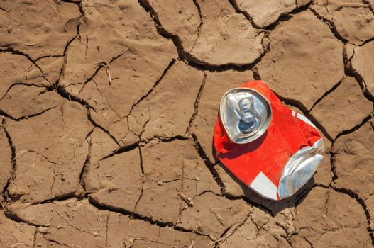 Empty soda can on dry soil