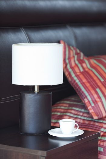 bed with a pillow, a cup of tea on the bedside table and lamp