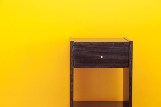 bedside table against a yellow wall in the apartment