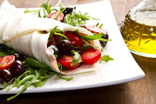 mozzarella roll with tomatoes,olives and salad on wood