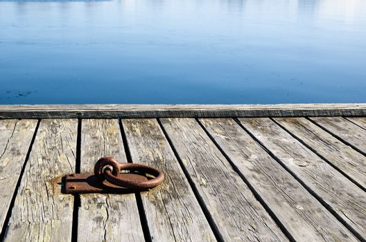 A rusty mooring loop at a wooden pier in sunlight