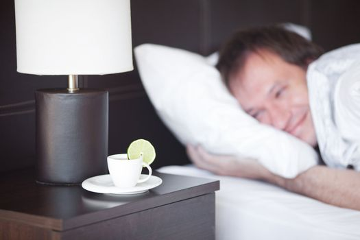 man sleeping on a bed, a cup of tea on the bedside table and lam