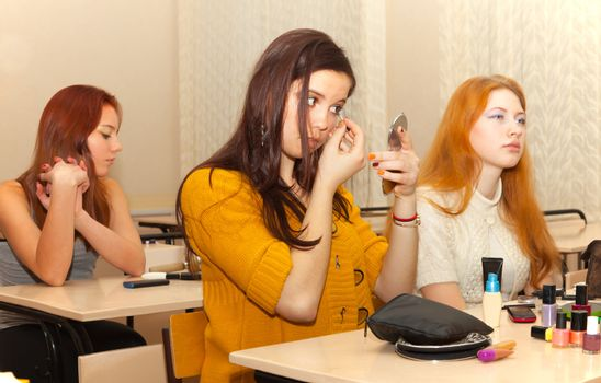 girls in the classroom during recess apply makeup