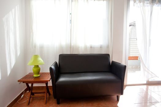 black sofa and a lamp on the bedside table on a background of cu