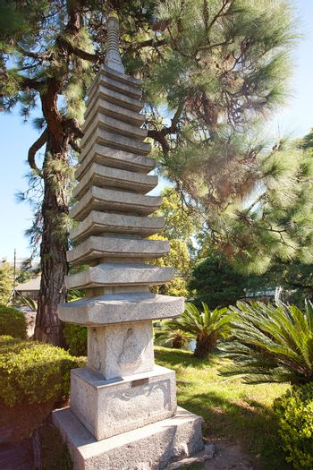 stone pagoda on the background of green trees
