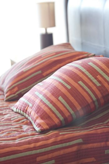 bed with a pillow, bedside table and lamp