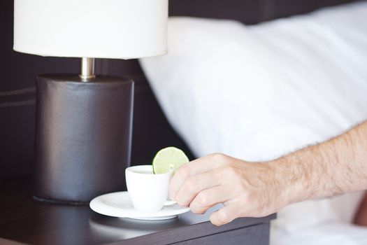 man hand, a cup of tea on the bedside table and lamp