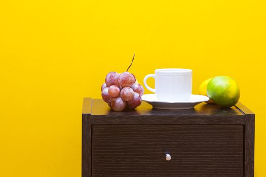 bedside table,fruits and cup against a yellow wall in the apartm