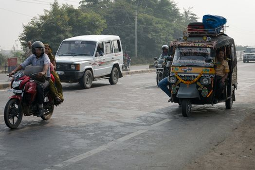 Overloaded motorcycles and tuk-tuks on covered by haze route, Ce
