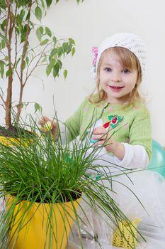 Cute girl enjoying green plants at spring