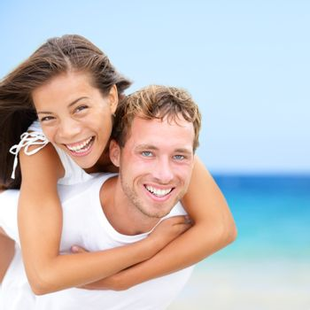 Happy couple on beach fun summer vacation. Multiracial Young newlywed couple piggybacking smiling joyful elated in happiness concept on tropical beach with blue water, sky. Asian woman, Caucasian man.