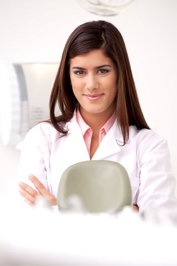 A young woman dentist smiling looking at the camera