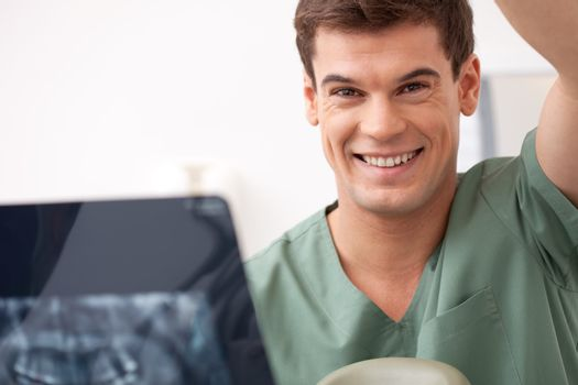Dentist with xray in hand, smiling at the camera