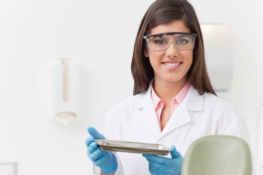 Smiling beautiful dentist holding tray of dental instruments