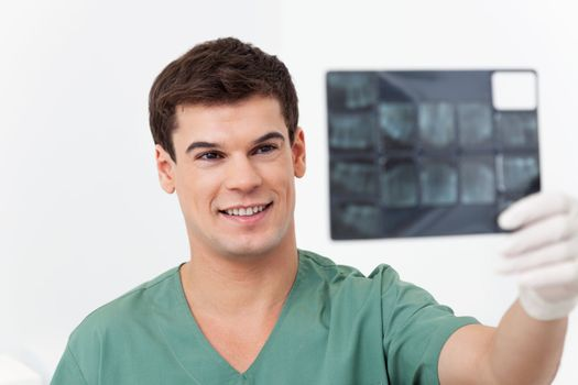 Young smiling doctor analyzing a dental X-Ray detail