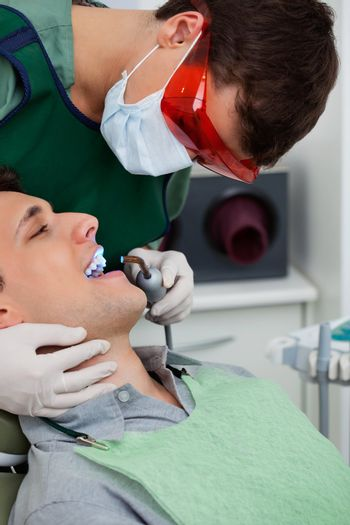 Male orthodontist working on male patient with ultraviolet light
