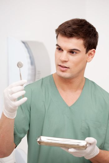 Young male dentist inspecting mirror and holding stainless steel tray