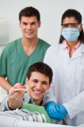 Male patient showing dental molds with dentist standing in background with her colleague