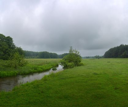 Green River flowing through green field on a summer morning