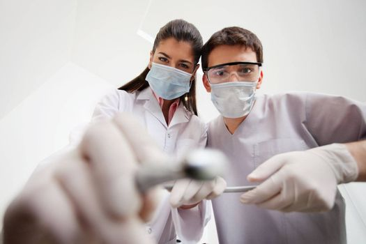 Female dentist and technician with cleaning tools