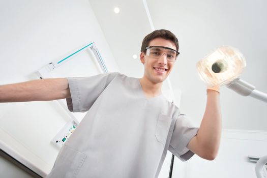 Young male dental assistant smiling and adjusting the lamp