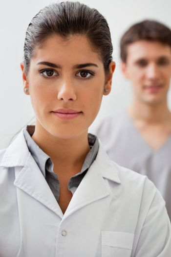 Portrait of confident female doctor with practitioner standing in background