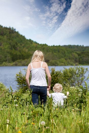 A mother walking in a meadow with a young toddler son