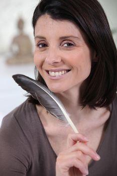 woman holding a bird plume