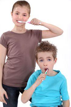 little boy and girl brushing their teeth