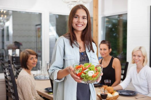 Portrait of happy female holding bowl of vegetables while her friends sitting in background