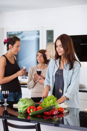 Pretty female cutting vegetables while her friends having drink in background
