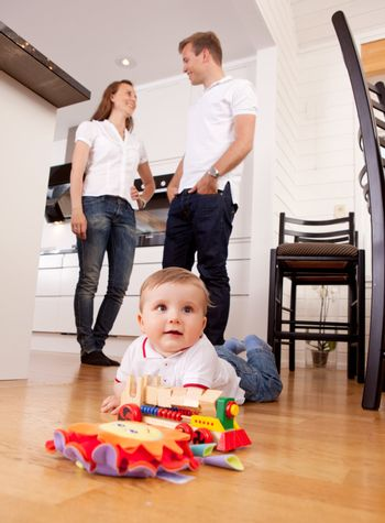 A young child boy playing on the kitchen floor with happy parents talking in the background